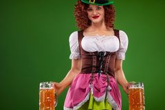 St Patricks Day. Young Oktober fest waitress, wearing a traditional Bavarian dress, serving big beer mugs on green. Half-length portrait of young redhead woman royalty free stock photo
