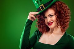 St Patrick Day. Portrait of young ginger woman leprechaun, wearing grenn dress and hat wich clover. Stock Image