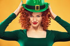 St Patrick Day. Portrait of young ginger woman leprechaun, wearing grenn dress and hat wich clover. Stock Images