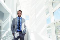 Half length portrait of a young smiling businessman dressed in corporate clothing with hands in pockets standing in modern space Royalty Free Stock Photos