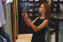 Half length portrait of a young woman shopper making photo on digital tablet camera of a men shirt while standing in store Royalty Free Stock Photos
