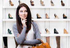 Half-length portrait of young woman in shopping center. Portrait of woman in shopping center in the section of female stylish shoes. Concept of consumerism and Royalty Free Stock Photography
