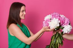 Half length shot of lady, faceless person give her big beautiful bouquet of flowers, being photographed on yellow studio. Background, being happy to recive stock image