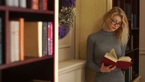 Half-length view of the beautiful girl with glasses reading the book in the library. Half-length view of the beautiful girl with glasses reading the book in the stock footage