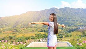 Half length of young Asian woman feeling free with arms wide open at beautiful trees and mountains on blue sky with morning. Sunlight royalty free stock images