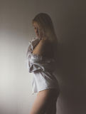 Half light. Blond woman standing by the wall in half light with her shirt off shoulders royalty free stock image