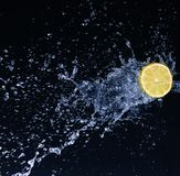 Half a lime falling into the water isolated on a black. Background royalty free stock image