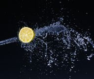 Half a lime falling into the water isolated on a black. Background stock photos