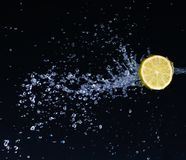 Half a lime falling into the water isolated. On a black background royalty free stock photography