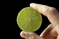 Half lime in the hand of a man royalty free stock photography