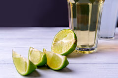 Half of lime with slices and glass of lemonade on a wooden white table. Central focus and copy space. Stock Photo