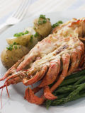 Half a Lobster Thermidor with New Potatoes. And Asparagus Spears stock photography