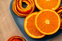 A half mandarin and peel of spiral on a plate. Close-up. Soft focus. Top view. A tangerine is served on a blue plate with a decor of a peel citrus. A half stock photography