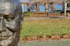 Half metal head. Half metal statue head over public park lanscape Stock Photo