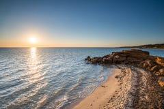 Half Moon Bay durante la puesta del sol en la playa de Brighton de Melbourne, Australia Foto de archivo