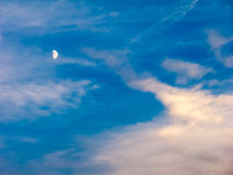 Half moon in a blue cloudy sky Stock Photo