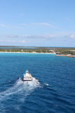 Half Moon Cay in the Bahamas. View of beach at Half Moon Cay in the Bahamas with boat approaching shore Royalty Free Stock Image