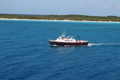 Half Moon Cay in the Bahamas. View of beach at Half Moon Cay in the Bahamas with boat approaching Stock Images