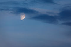 Half Moon glows in blue sky at twilight Royalty Free Stock Images