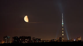 Half moon over TV tower and city in summer night Royalty Free Stock Images