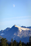 Half moon reveals itself over Alaskan mountaintops on  summer evening Royalty Free Stock Images