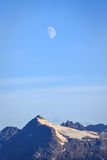 Half moon shines down on snow-capped mountain top  Alaska. Half moon shines down on snow-capped mountain top at evening in summertime Alaska Royalty Free Stock Photos