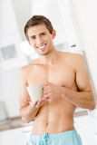 Half-naked cool man with cup of coffee at kitchen Stock Image