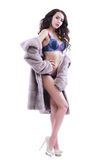 Half-naked girl in a fur coat on a white background Royalty Free Stock Images