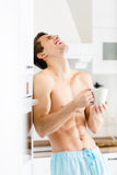 Half-naked male with cup of coffee at kitchen stock photos