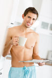 Half-naked male with cup of tea reads newspaper Royalty Free Stock Image