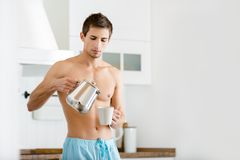 Half-naked male pouring tea at the kitchen. Half-naked male pouring coffee at the kitchen, having breakfast Stock Images