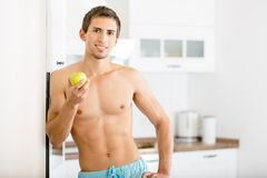 Half-naked man with apple. Standing near the fridge at the kitchen Royalty Free Stock Photography