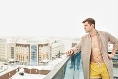 Handsome young man relaxing on winter snowy terrace after getting steamed bath. Half naked man in bathing shorts and bathrobe stands on top roof of skyscraper stock photo