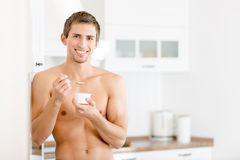 Half-naked man eating yoghurt Royalty Free Stock Photo