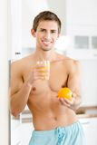 Half-naked man with glass of juice and orange Stock Image