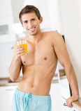 Half-naked man with glass of juice Royalty Free Stock Photography