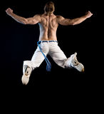 Half naked man in jump. Half naked man in the air from behind.  Isolated jump on black Royalty Free Stock Photo