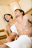 Half-naked man and lady relaxing in sauna Royalty Free Stock Images