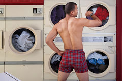 Half-naked Man in Laundromat. Muscular man in boxer shorts looks at wristwatch in laundromat stock image