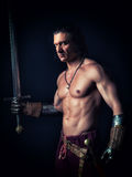 Half-naked man with a sword in medieval clothes. On a dark background Royalty Free Stock Images