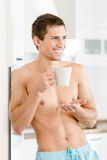 Half-naked pretty man with cup of coffee at kitchen Stock Images