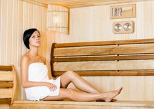 Half-naked woman relaxing in sauna Stock Photos