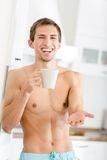 Half-naked young male with cup of coffee at kitchen Stock Image