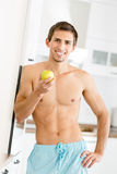 Half-naked young man with apple Stock Photo