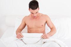 Half naked young man in bed  looking down at his underwear Stock Images