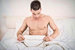 Half naked young man in bed  looking down at his underwear Stock Photo