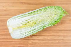 Half of napa cabbage head on a wooden cutting board. Half of head napa cabbage also known as chinese cabbage, cut along on the bamboo wooden cutting board stock images