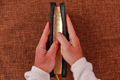Half open bible in his hand. The half open bible in his hand Royalty Free Stock Photo