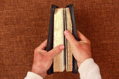 Half open bible in his hand. The half open bible in his hand Royalty Free Stock Photography