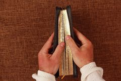 Half open bible in his hand. The half open bible in his hand Stock Photography